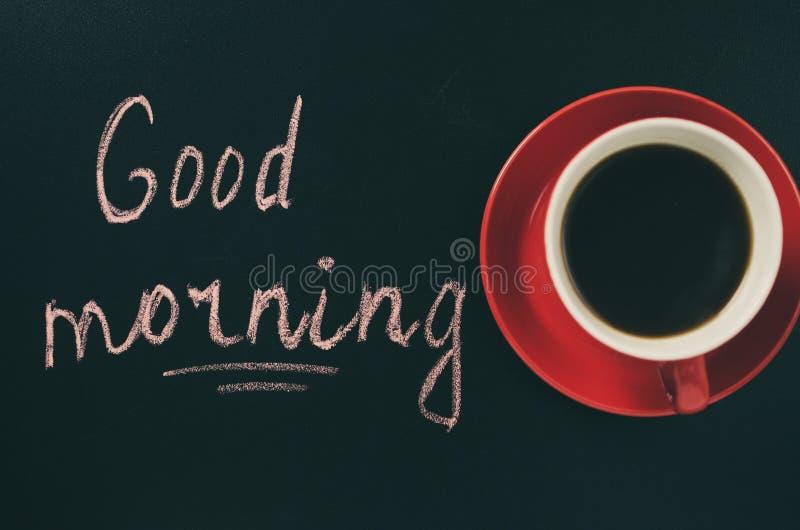 Xícara de café em um fundo escuro e no bom dia da inscrição imagem de stock