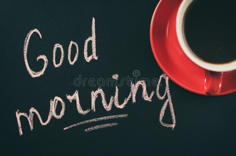 Xícara de café em um fundo escuro e no bom dia da inscrição foto de stock