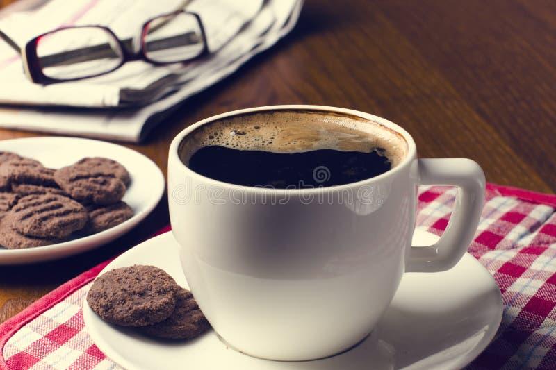 Xícara de café em uma tabela de madeira com biscoitos, vidros e jornal fotografia de stock