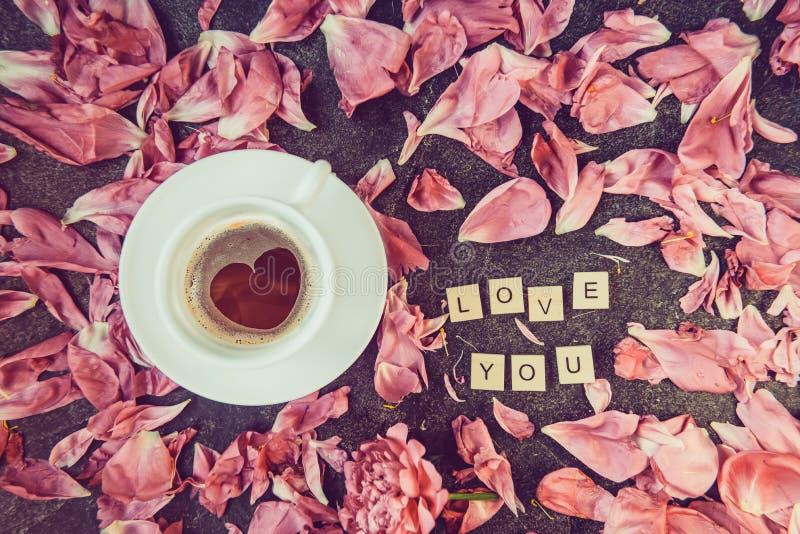 Xícara de café de Flatlay com o teste padrão e a mensagem da forma do coração eu te amo soletrados em blocos de madeira com as pé imagem de stock