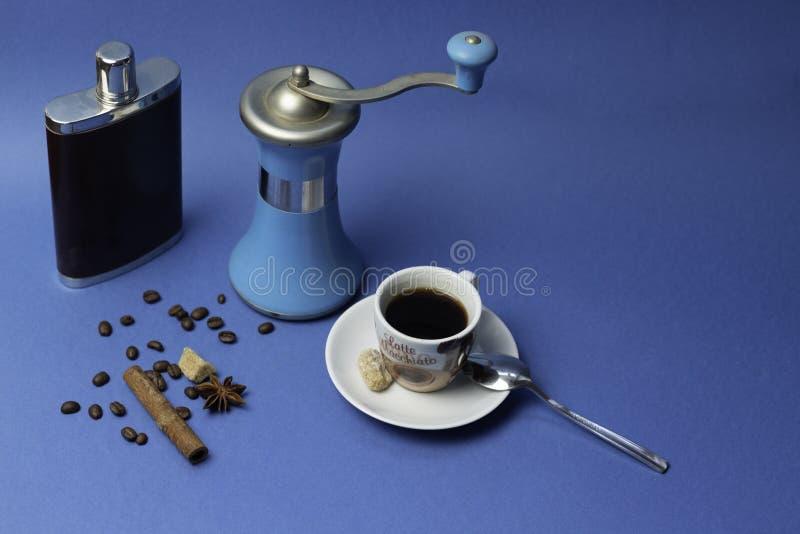 Xícara de café, garrafa com conhaque e moedor de café do manual em um fundo azul imagens de stock