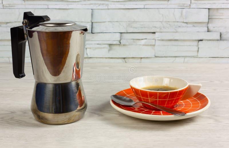 Xícara de café moderna e um fabricante de café em uma tabela de madeira foto de stock royalty free