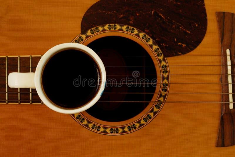 Xícara de café na guitarra acústica imagem de stock