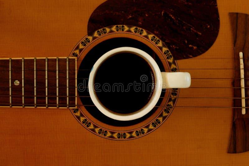 Xícara de café na guitarra acústica fotografia de stock royalty free