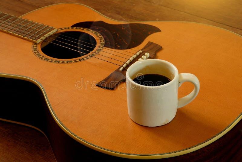 Xícara de café na guitarra acústica fotos de stock