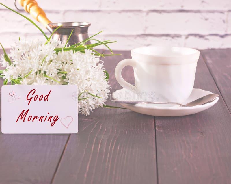 A xícara de café na tabela e em um ramalhete branco das flores e com um cartão a inscrição é um bom dia imagem de stock royalty free