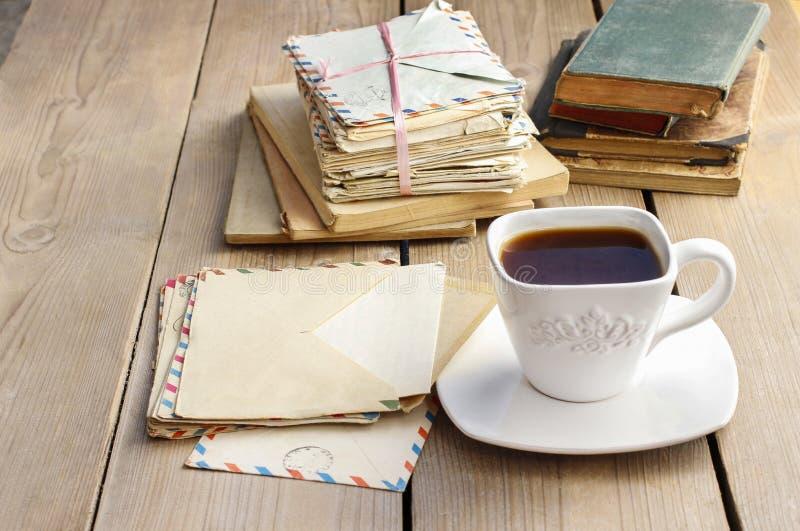 Xícara de café na tabela de madeira Livros do vintage e pilha das letras imagem de stock