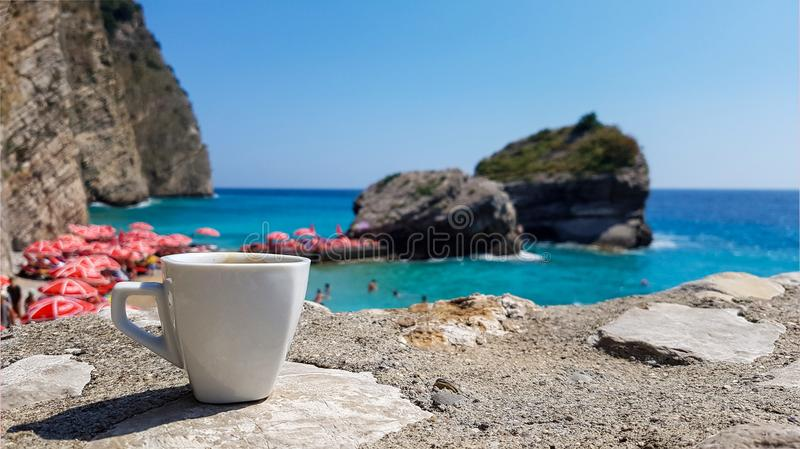 Xícara de café no fundo da paisagem bonita do mar com linha pitoresca do mar, da praia e do horizonte, Montenegro imagens de stock