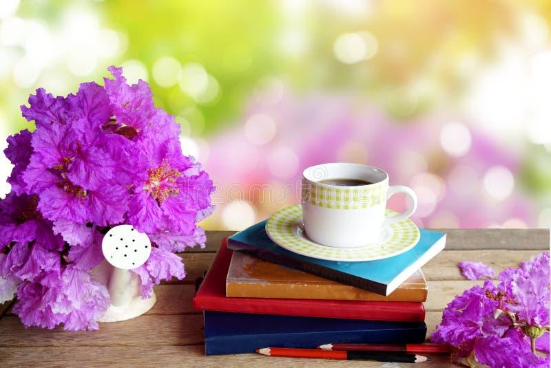 A xícara de café, os livros, os lápis e a mola roxa florescem sobre o fundo da natureza foto de stock