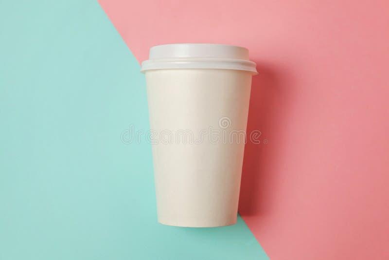 Xícara de café de papel no fundo azul e cor-de-rosa foto de stock royalty free