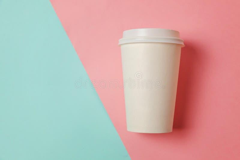 Xícara de café de papel no fundo azul e cor-de-rosa fotografia de stock royalty free