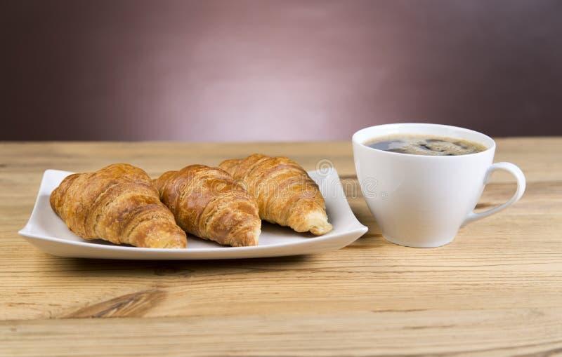 Xícara de café quente com os croissant no restaurante imagem de stock