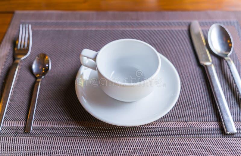 Xícara de café vazia com os acessórios na tabela de café da manhã imagem de stock royalty free