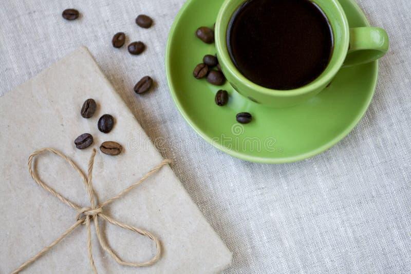 Xícara de café verde com feijões e caderno de café imagens de stock