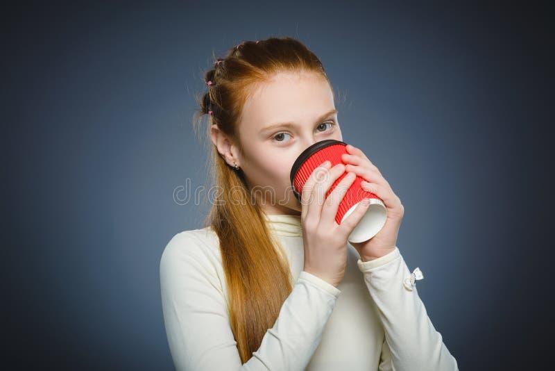 Xícara de café vermelha da bebida do adolescente isolada no fundo cinzento fotos de stock