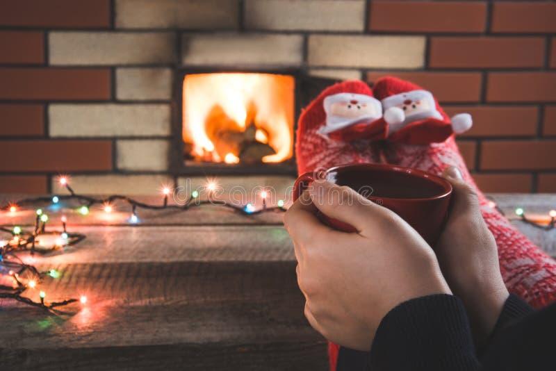 Xícara de café vermelha na mão fêmea pela chaminé A fêmea relaxa pelo warmfire em peúgas do vermelho do Natal Feriado do Natal imagens de stock