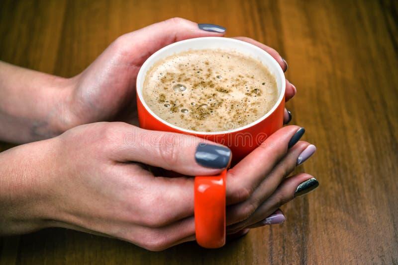 Xícara de café vermelha nas mãos foto de stock