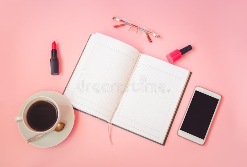 Xícara de café, vidros, batom, verniz para as unhas, smartphone e diário no fundo cor-de-rosa Vista superior, espa?o da c?pia foto de stock