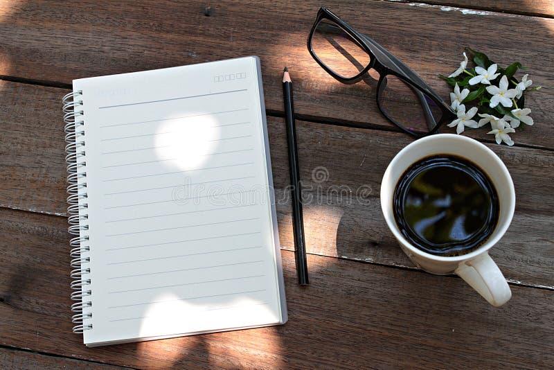 Xícara de café, vidros, papel do caderno, lápis e flores brancas no fundo de madeira fotos de stock royalty free