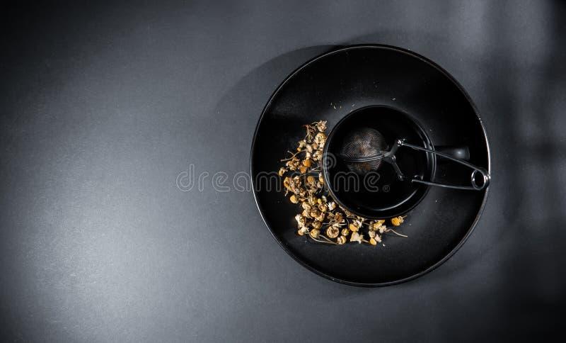 Xícara de chá de camomila com pétalas secas e palha, isolada sobre fundo preto cinzento imagens de stock