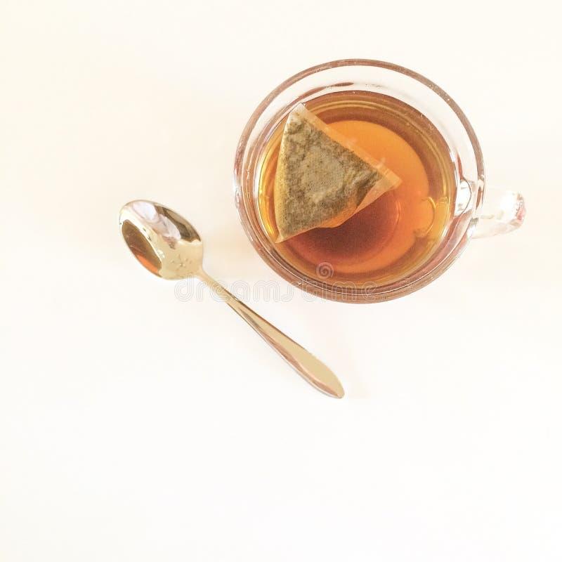 Xícara de chá no fundo branco com colher imagem de stock