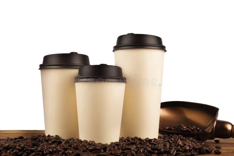 Xícaras de café e feijões de café isolados em um fundo branco imagens de stock royalty free