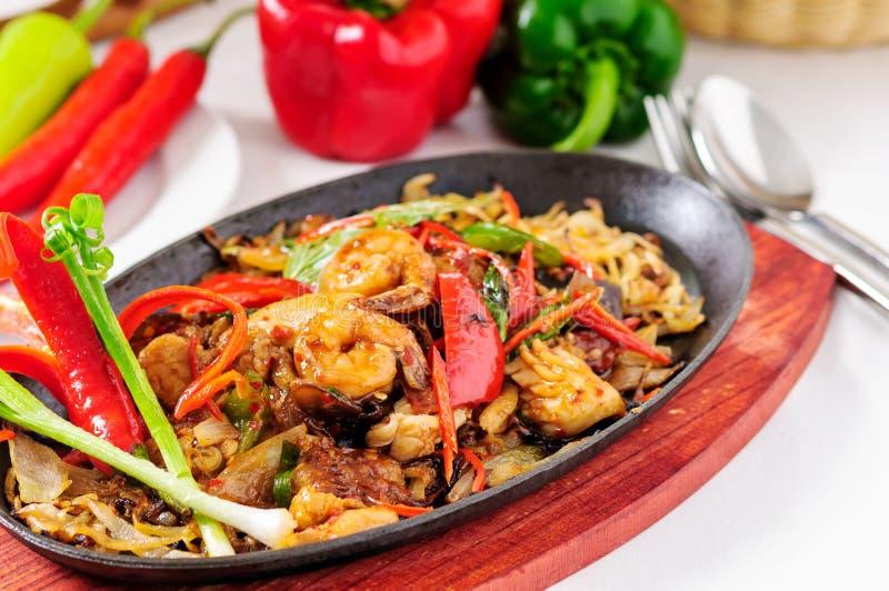 Spicy fried seafood on a hot pan. Xāh̄ār thale p̄hạd p̄hĕd bn kratha r̂xn.. S̄īs̄ạn s̄ds̄ı læa tkt royalty free stock photo