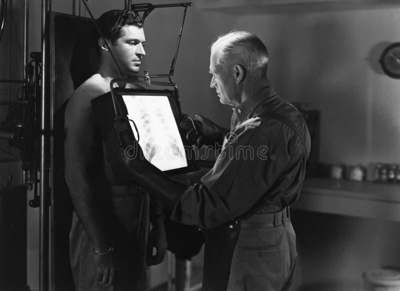 X射线辐射患者胸口的医生(所有人被描述不更长生存,并且庄园不存在 供应商保单那里w 免版税库存图片