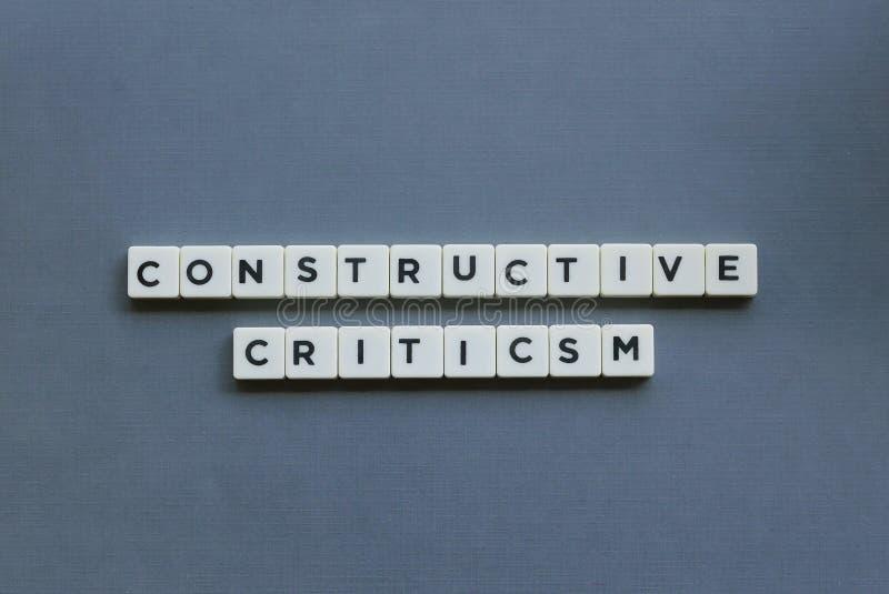 '  Εποικοδομητική κριτική '  λέξη φιαγμένη από τετραγωνική λέξη επιστολών στο γκρίζο υπόβαθρο στοκ εικόνες