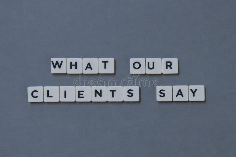 ' Чему наши клиенты говорят ' слово сделанное квадратного слова письма на серой предпосылке стоковые изображения rf