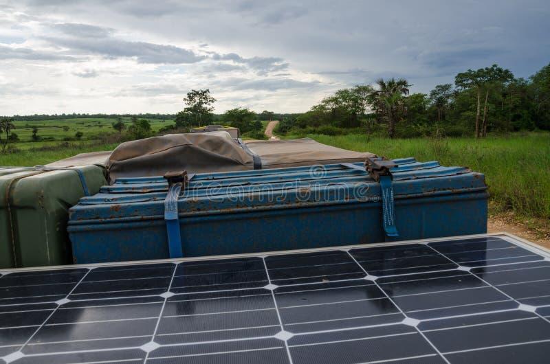 4x4有便壶罐头、太阳电池板、屋顶顶面帐篷和储藏盒的越野车屋顶在泥铺跑道在安哥拉,非洲 免版税图库摄影