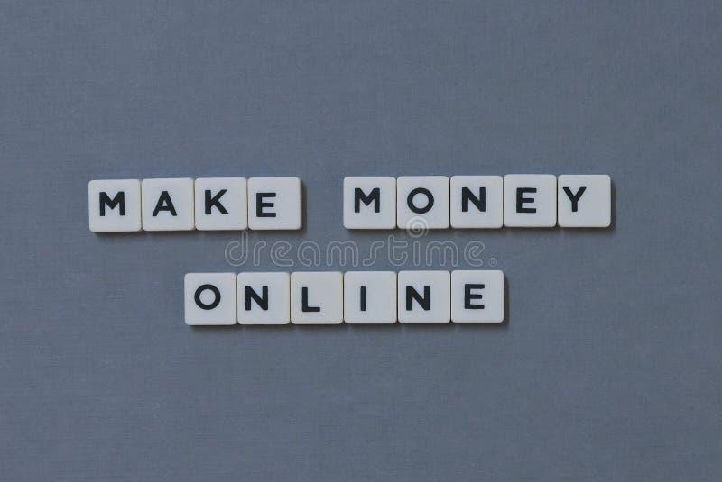 ';做金钱网上';词由方形的信件词制成在灰色背景 免版税库存图片