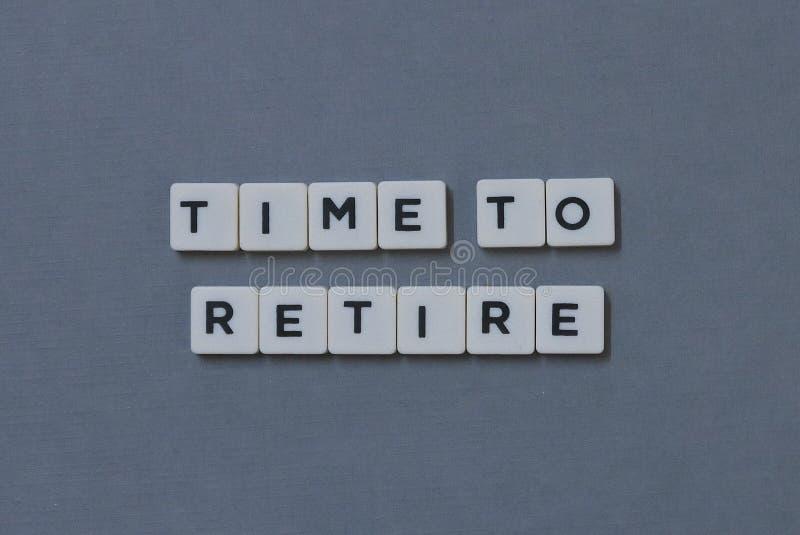 '时刻退休'词由方形的信件词制成在灰色背景 免版税库存图片