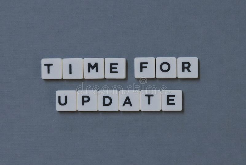 '更新&#x27的时刻;词由方形的信件词制成在灰色背景 库存图片