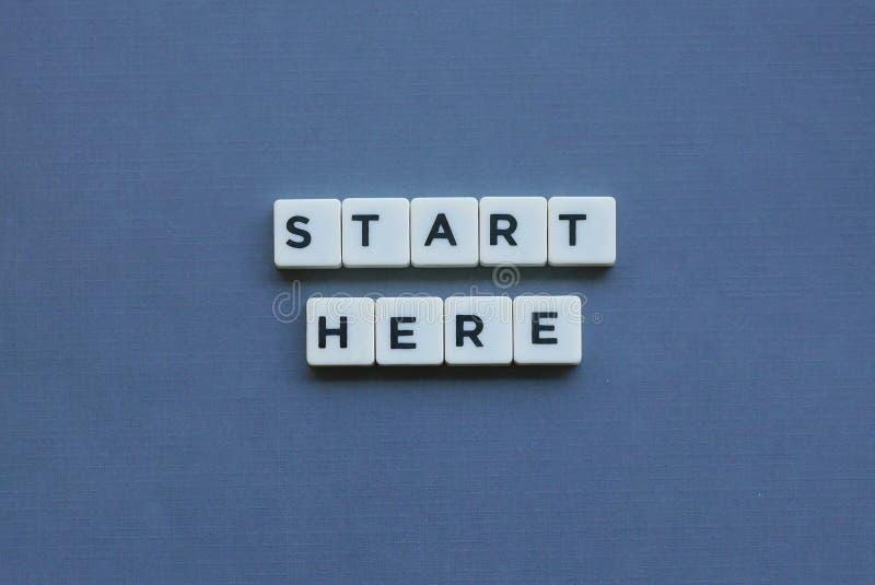 ' Begin hier ' woord van vierkant brievenwoord wordt gemaakt op grijze achtergrond die royalty-vrije stock foto
