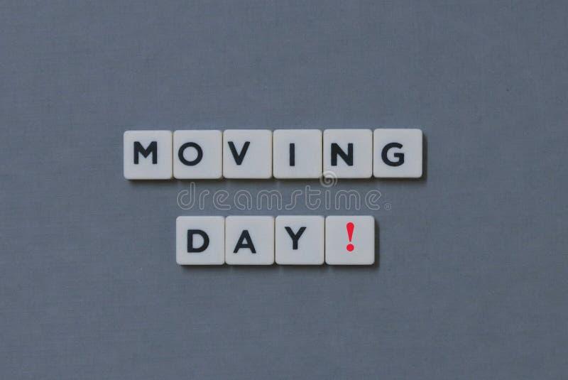 ' Bewegende Dag! ' woord van vierkant brievenwoord wordt gemaakt op grijze achtergrond die stock afbeeldingen