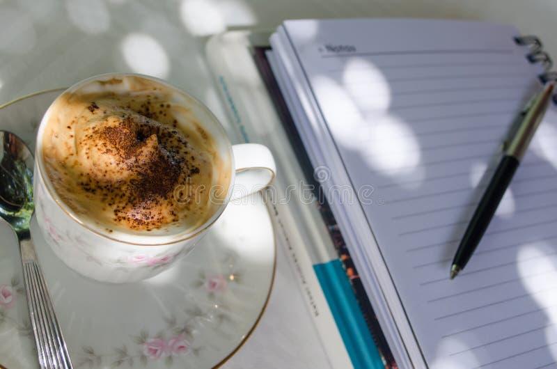 X?cara de caf? com creme e caderno em uma tabela exterior imagens de stock