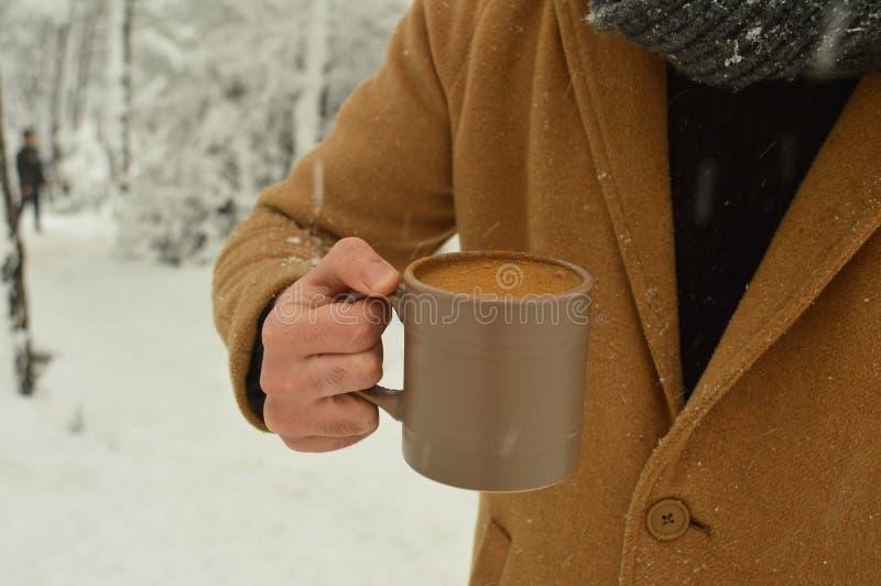 X?cara de caf? masculina da terra arrendada da m?o com fundo nevado imagem de stock royalty free