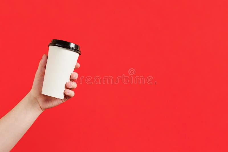 X?cara de caf? ou ch? de papel em um fundo vermelho O modelo da m?o masculina que guarda o copo de papel isolou-se Modelo da vist foto de stock royalty free