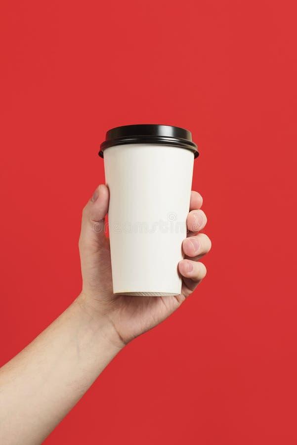 X?cara de caf? ou ch? de papel em um fundo vermelho O modelo da m?o masculina que guarda o copo de papel isolou-se Modelo da vist imagem de stock royalty free