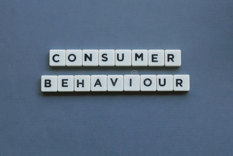 ' Consumentengedrag ' woord van vierkant brievenwoord wordt gemaakt op grijze achtergrond die stock fotografie