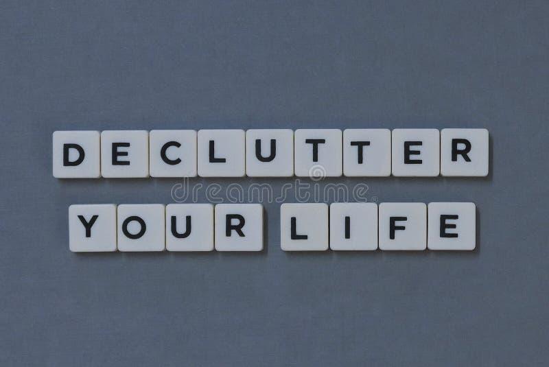 ' Declutter la vostra vita ' parola fatta della parola quadrata della lettera su fondo grigio fotografia stock