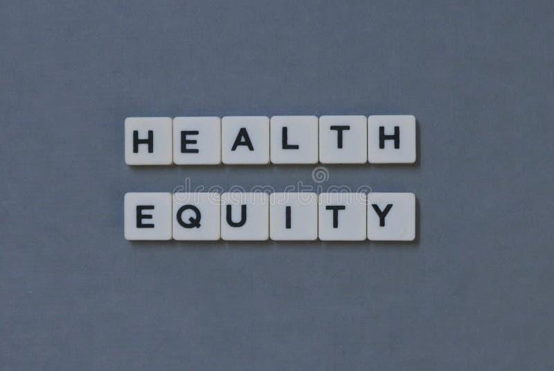 ' Equidade ' da saúde; palavra feita da palavra quadrada da letra no fundo cinzento imagens de stock royalty free