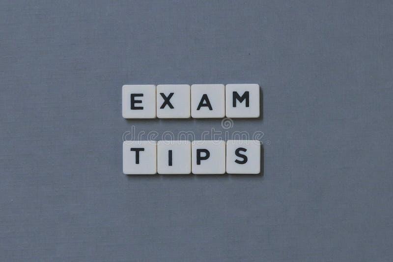 ' Examenuiteinden ' woord van vierkant brievenwoord wordt gemaakt op grijze achtergrond die royalty-vrije stock afbeeldingen