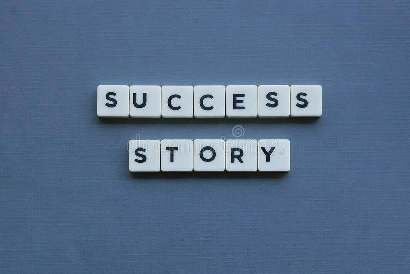 ' Framgångssaga ' ord som göras av fyrkantigt bokstavsord på grå bakgrund arkivfoton