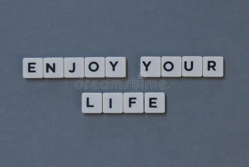 ' Genießen Sie Ihr Leben ' Wort gemacht vom quadratischen Buchstabewort auf grauem Hintergrund stockfotos