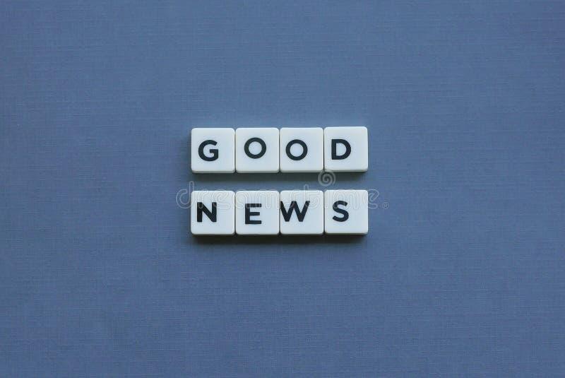 ' Goed Nieuws ' woord dat van vierkant brievenwoord wordt gemaakt op grijze achtergrond stock foto's
