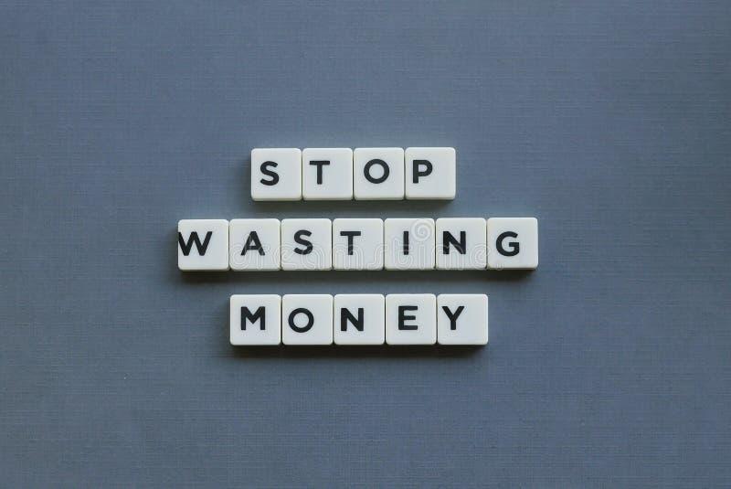 ' Hören Sie auf, Geld ' zu vergeuden; Wort gemacht vom quadratischen Buchstabewort auf grauem Hintergrund lizenzfreie stockfotografie