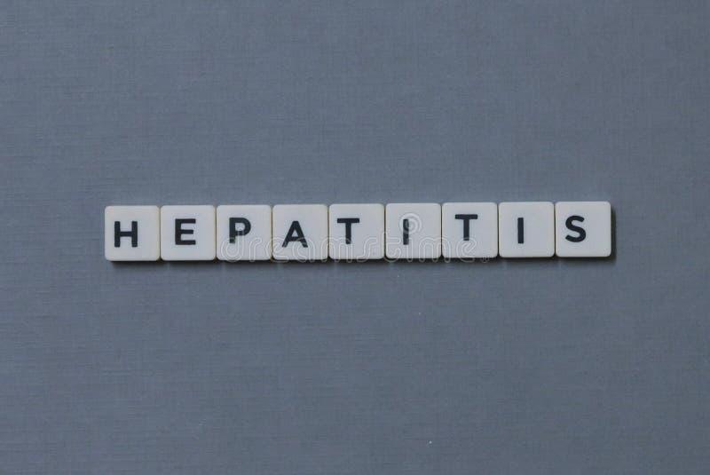 ' Hepatitis ' Wort gemacht vom quadratischen Buchstabewort auf grauem Hintergrund lizenzfreie stockfotos