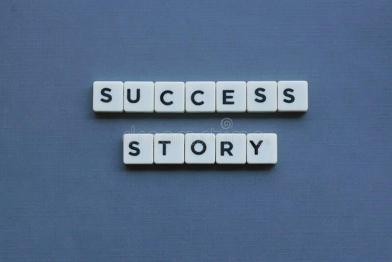 ' História de sucesso ' palavra feita da palavra quadrada da letra no fundo cinzento fotos de stock
